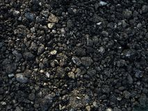 Fresh blacktop gravel ground Road material. Blacktop material on the ground in a gravel form. Used for making roads parking lots, paving and construction Royalty Free Stock Photos