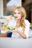 Fresh blonde woman eating salad outdoor Stock Images