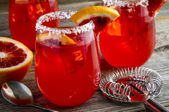 Fresh Blood Orange Margaritas. Garnished with blood orange slice sitting on rustic wooden table with hawthorne strainer and bar spoon Royalty Free Stock Images