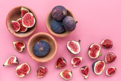 Fresh blue figs in bowls on pink background top view Royalty Free Stock Images