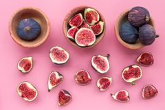 Fresh blue figs in bowls on pink background top view Royalty Free Stock Image