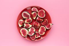 Fresh blue figs sliceson plate on pink background top view copyspace Royalty Free Stock Image