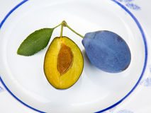 Fresh blue plum arranged on the white plate Stock Photography