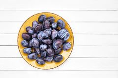 Fresh blue plums in yellow plate on white wooden table. Top view, copy space Royalty Free Stock Photography