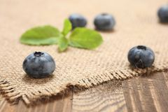 Fresh blueberries on a background of burlap and wooden Stock Photography