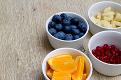 Fresh blueberries, banana, pomegranate and orange slices in bowls stock images