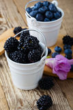 Fresh blueberries and blackberries in decorative ceramic buckets. On wooden table Stock Images