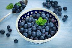 Fresh Blueberries in a bowl. On blue background Stock Image