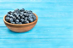 Blueberries in bowl. Fresh blueberries in a bowl on a blue table Stock Photos