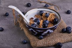 Fresh blueberries and a bowl with cornflakes and milk on a gray concrete stock image