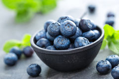 Fresh Blueberries in a bowl on dark background, top view. Juicy wild forest berries, bilberries. Royalty Free Stock Photo