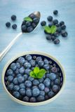 Fresh Blueberries in a bowl. On blue background Royalty Free Stock Photography