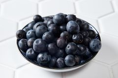 Fresh Blueberries in a bowl. On white tile hexagonal bench, wholesome fresh fruit for healthy living Royalty Free Stock Images