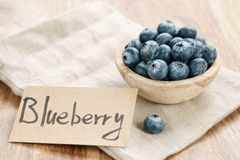 Fresh blueberries in bowl with paper card on wood table with sack cloth Royalty Free Stock Photos