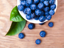 Fresh blueberries in a bowl. On wooden background Royalty Free Stock Image