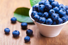 Fresh blueberries in a bowl. On wooden background Royalty Free Stock Images