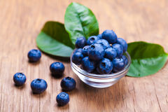 Fresh blueberries in a bowl. On wooden background Stock Photos