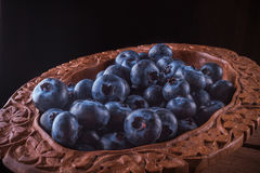Fresh blueberries in brown cup. Close view from above on handful of ripe and fresh blueberries in brown wooden cup and some blueberries sprinkled on white wooden Royalty Free Stock Images