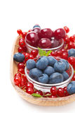 Fresh blueberries, cherries and red currants in a wooden bowl Royalty Free Stock Images