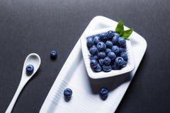 Fresh blueberries fruits on white ceramic bowl over the black ba Royalty Free Stock Image