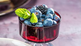Fresh blueberries in a glass bowl on black background. Shallow depth of field. Close-up stock image