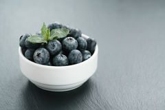 Fresh blueberries with mint leaves in white bowl on slate board Royalty Free Stock Photos