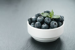 Fresh blueberries with mint leaves in white bowl on slate board Royalty Free Stock Photography