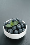 Fresh blueberries with mint leaves in white bowl on slate board Stock Photography