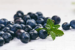 Fresh blueberries with mint on a wooden white table. Natural antioxidant. Concept of healthy food. Organic superfood Royalty Free Stock Images