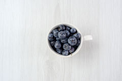 Fresh blueberries in mug on wooden background. Fresh blueberries in mug on wooden gray background Royalty Free Stock Photo