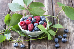 Fresh blueberries and raspberries in a bowl on a wooden table. Fresh assorted berries on wooden table in small ceramic dishes Stock Image