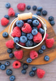 Fresh blueberries and raspberries in a  bucket. Fresh blueberries and raspberries in a white bucket on  wooden background Stock Photos