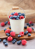 Fresh blueberries and raspberries in a  bucket Royalty Free Stock Photo
