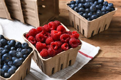 Fresh Blueberries and Raspberries. Closeup of containers of fresh picked blueberries and raspberries Royalty Free Stock Photography