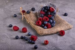 Fresh blueberries and raspberries scattered from a transparent bucket on a gray concrete stock photography