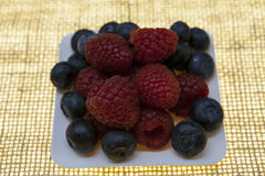 Fresh blueberries, raspberries on a white plate, closeup on a plate on a linen background closeup. Background for confectionery, c. Afe fresh berries for pastry Stock Image