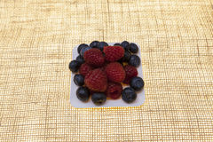 Fresh blueberries, raspberries on a white plate, closeup on a plate on a linen background closeup. Background for confectionery, c. Afe fresh berries for pastry Royalty Free Stock Image