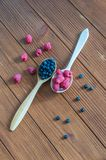 Fresh blueberries and raspberries in wooden spoon. Dark wood background Royalty Free Stock Photo