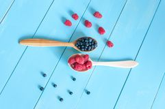 Fresh blueberries and raspberries in wooden spoon. Light blue wood background Royalty Free Stock Photo