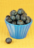 Fresh Blueberries in Small Bowl on Yellow Stock Photo
