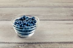 Fresh blueberries in small transparent glass bowl placed on wood Royalty Free Stock Photo
