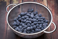 Fresh blueberries in stainless steel colander. On a wood surface Stock Image