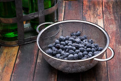 Fresh blueberries in stainless steel colander. On a wood surface Stock Photo