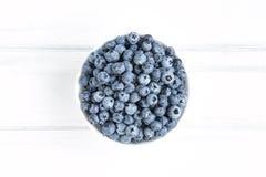 Fresh blueberries in white bawl on white wooden table. Flat lay, top view. Fresh blueberries in white bawl on white wooden table. Minimalistic flat lay royalty free stock image