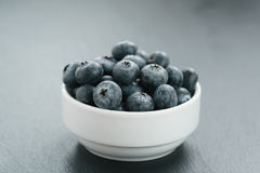 Fresh blueberries in white bowl on slate board Stock Photo
