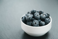 Fresh blueberries in white bowl on slate board Stock Photography