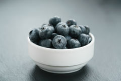 Fresh blueberries in white bowl on slate board Royalty Free Stock Images