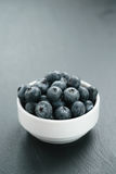 Fresh blueberries in white bowl on slate board Royalty Free Stock Photography