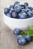 Fresh blueberries in white bowl on wood table Royalty Free Stock Photos
