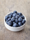 Fresh blueberries in white bowl on wood table Royalty Free Stock Image
